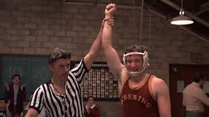 Robin Williams as Garp in a wrestling match scene with Garp's writer John Irving doing as cameo as the referee.