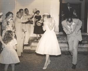 Mama and Daddy dodging rice as they dash for the getaway car after their 1956 wedding.